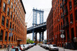 Manhattan bridge seen from a red brick buildings in Brooklyn street in perspective, New York, USA. Beautiful classic apartments in New York City. Beautiful american street. Famous view.