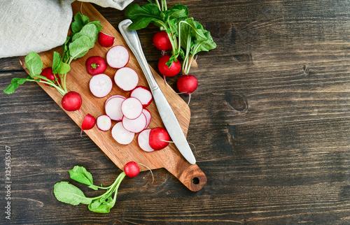 Fototapeta radish vitamin salad, sliced fresh radish on wooden Board. salad recipe with seasonal vegetables, healthy diet food. selective focus obraz
