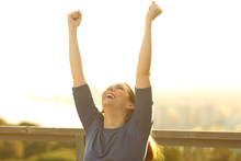 Excited Woman Raising Arms At ...