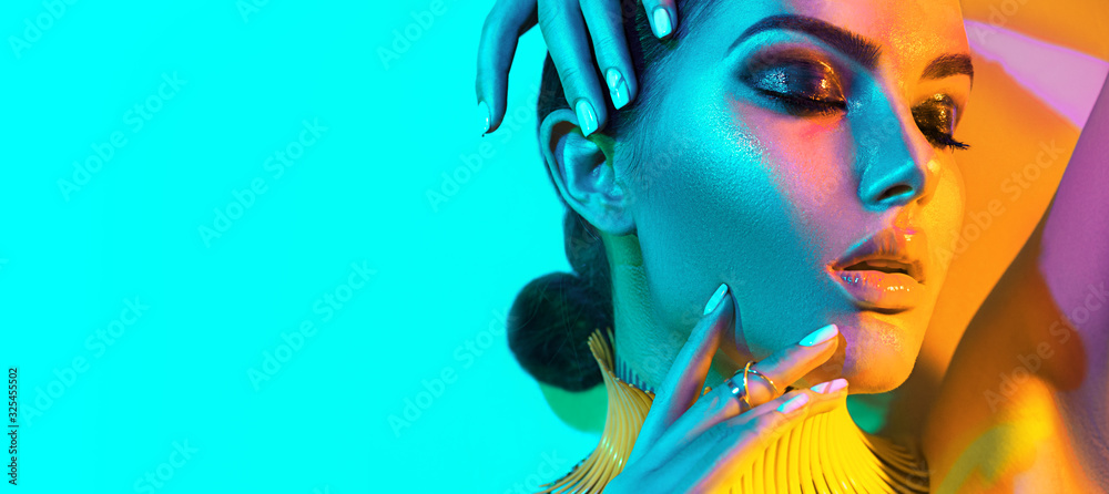 Fototapeta High Fashion model woman in colorful bright lights, portrait of beautiful sexy girl with trendy make-up and manicure. colorful neon skin, Art design, multicolor make up. Over blue background
