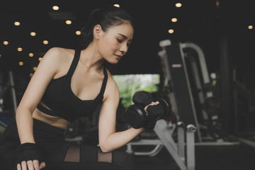 Fototapeta na wymiar athletic young pretty asian slim body woman in black sport bra exercise with dumbbell in fitness gym in background, bodybuilder, healthy lifestyle, exercise fitness, workout and sport training concept