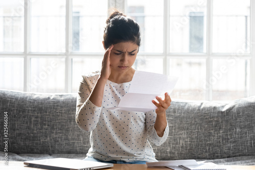 Frustrated indian woman sitting indoors holding letter reading bad news Fototapet