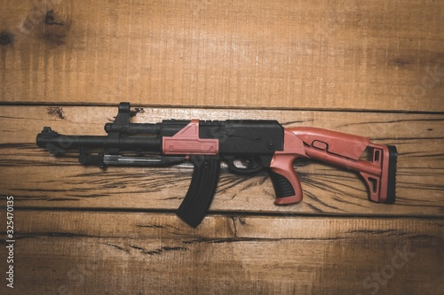 Valokuva High angle shot of a military firearm on a wooden surface