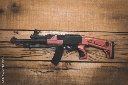 Fényképezés High angle shot of a military firearm on a wooden surface