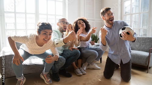 European guy holding ball enjoy football game with friends indoors Tableau sur Toile