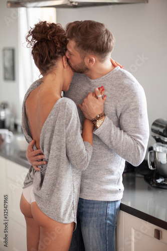 Fototapeta Romantic dance of loving couple in the kitchen. How lovely. obraz
