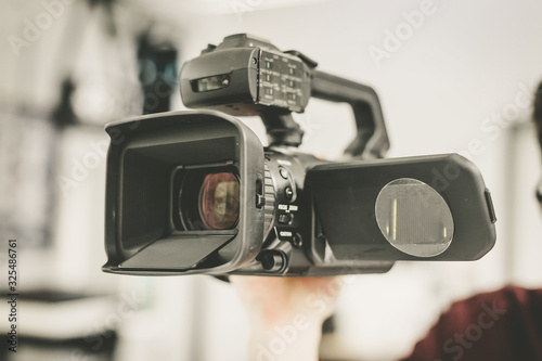 Fototapeta Professional film production: Male filmmaker is recording with a professional movie camera