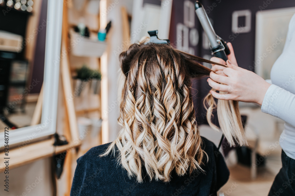 Fototapeta Beautiful hairstyle of young woman after dyeing hair and making highlights in hair salon.