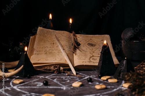 Obraz na plátně Open old book with magic spells, runes, black candles on witch table