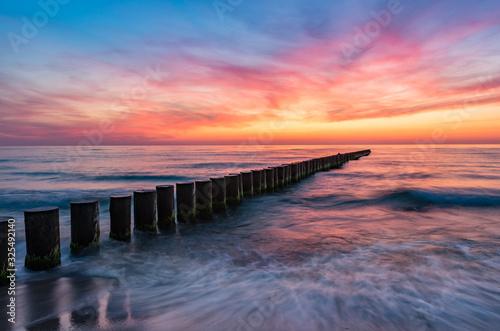 Obraz Baltic sea seascape at sunset, Poland, wooden breakwater and waves - fototapety do salonu