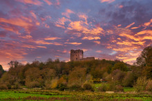 Ancient Ruins Of Dundonald Castle Scotland And A Blazing Red Sunset Sky.