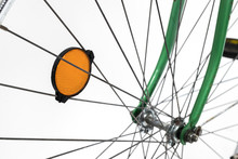 An Old Retro Looking Green Vintage City Bicycle For Women, Isolated On White Background. Detail Of Reflector On Spokes, So Called Cateye