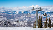 Skiers And Snowboarders Ascend The Elk Camp Chairlift At The Aspen Snowmass Ski Resort, In The Rocky Mountains Of Colorado On A Partly Cloudy Winter Day.