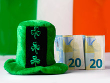 Green Hat With Shamrock, Irish National Flag In The Background Two Euro Banknotes Folded Making 2020 Year Saint Patrick Day Celebration.