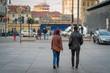 man and woman walking in Porta Palazzo market in Torino, Turin. View from the Piazza della Repubblica square. Turin, Italy