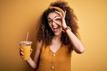 Young Beautiful Woman With Curly Hair And Piercing Drinking Healthy Orange Juice With Happy Face Smiling Doing Ok Sign With Hand On Eye Looking Through Fingers