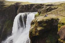Woman Sitting On Edge With Breathtaking View Of Fagrifoss Waterfall In Iceland. Lakagigar Landmark In Skaftafell National Park.