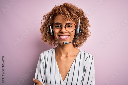 Obraz na plátně African american curly call center agent woman working using headset over pink background happy face smiling with crossed arms looking at the camera