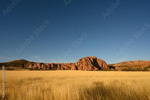 Fototapeta Dry Grassy Field And Red Rocks At Sunset obraz