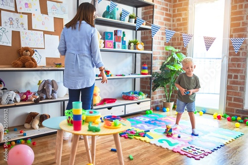 Young caucasian child playing at playschool with teacher Tableau sur Toile