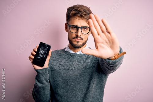 Valokuva Young man with beard wearing glasses holding broken and craked smartphone with o