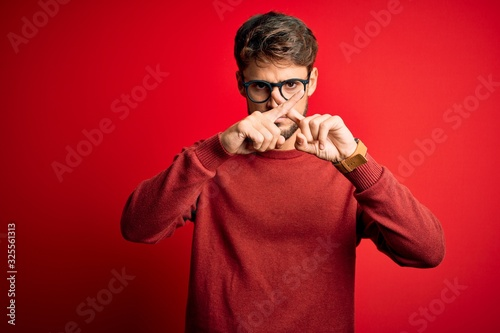 Valokuvatapetti Young handsome man with beard wearing glasses and sweater standing over red back