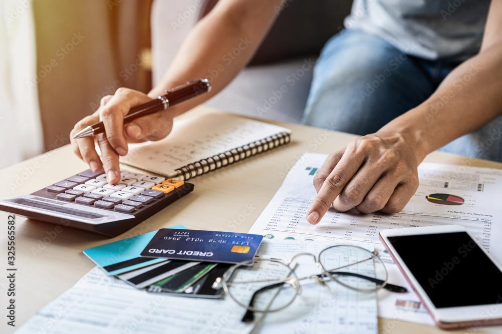 Fototapeta Young woman checking bills, taxes, bank account balance and calculating credit card expenses at home