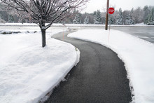 Winding Pedestrian Sidewalk With Snow Removed After Winter Snow
