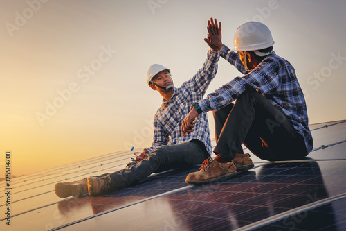 Obraz Electrical, instrument technician celebrate their work day done, maintenance electric system by shake hands at solar panel field  - fototapety do salonu