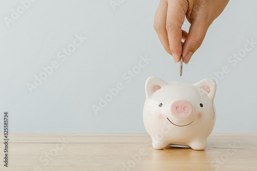 Fototapeta Concept of save money financial business investment. Hand of a man putting coins in piggy bank on wood table obraz