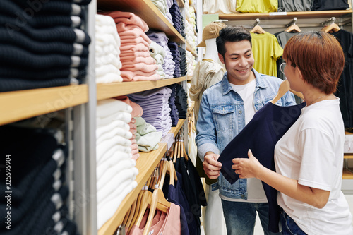 Fotografía Shop assistant helping handsome young Asian man with choosing casual t-shirt