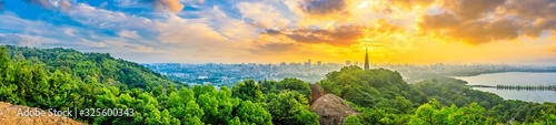 Panoramic city skyline and green mountains at sunrise in Hangzhou,China.