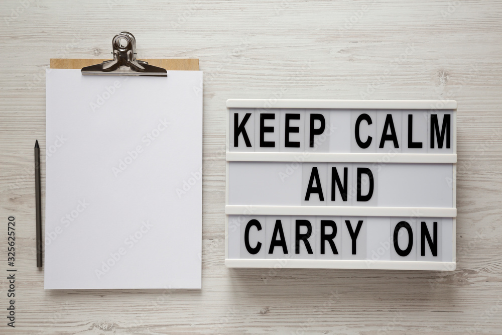 Fototapeta 'Keep calm and carry on' words on a modern board, clipboard with blank sheet of paper on a white wooden background, top view. Overhead, from above, flat lay.