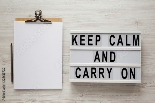 Fotografía 'Keep calm and carry on' words on a modern board, clipboard with blank sheet of paper on a white wooden background, top view