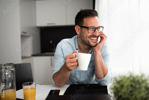 Leinwand Poster Handsome man having cup of coffee at home in the morning