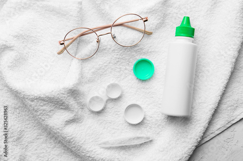 Photo Container with contact lenses, glasses, solution and tweezers on towel