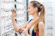 Woman choosing new glasses out of shelf in optician store