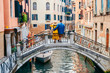 canvas print picture - couple standing on the bridge crossing venice canals