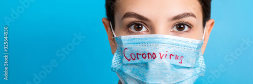 Portrait of pretty woman wearing medical mask with coronavirus text at blue background Fototapet