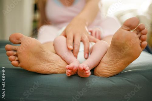 Photo Pieds de bébé entre les pieds de sa mère