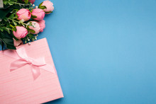 Gift Box With Pink Bouquet Of Roses On Blue Paper Background. Flat Lay.