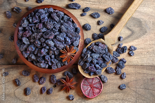 black raisins in a bowl on a wooden table Wallpaper Mural