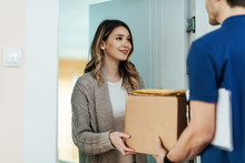 Smiling Woman Receiving A Package From Delivery Man At Home.