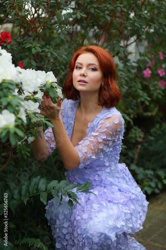 beautiful red-haired girl in arranger where azalea blooms in a colorful flying d Canvas Print