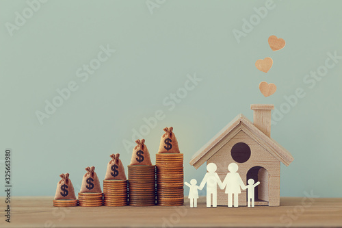 Mini house and heart, family members, US money bags on rows of rising coins on table Fototapet