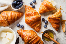 Fresh Croissants With Blueberries, Butter And Honey, Gray Background, Top View.