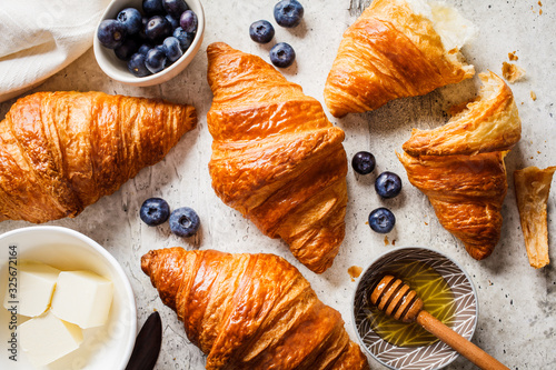 Fotografia Fresh croissants with blueberries, butter and honey, gray background, top view