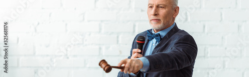 Photo panoramic shot of auctioneer holding microphone and pointing with gavel during a