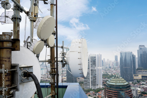 Closeup of a radio mast with cityscape background Canvas Print