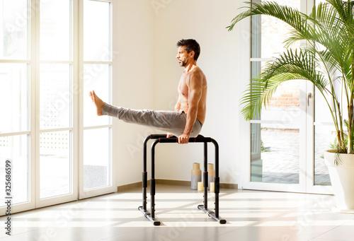 Fotografia Fit man doing V sit exercises on parallel bars